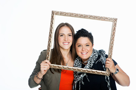 Lesbian couple holding picture frame against white background