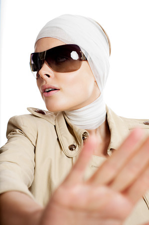 Young woman in sunglasses and bandages after cosmetic surgery