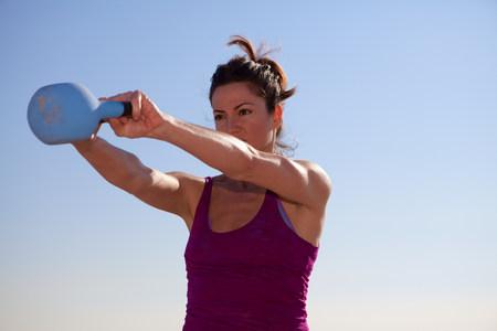 levantar peso: Mujer trabajando con pesas rusas LANG_EVOIMAGES
