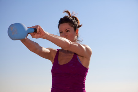 exerting: Woman working out with kettlebell