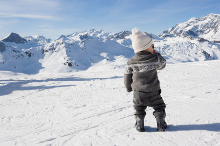 Young boy standing looking at mountains in snow LANG_EVOIMAGES