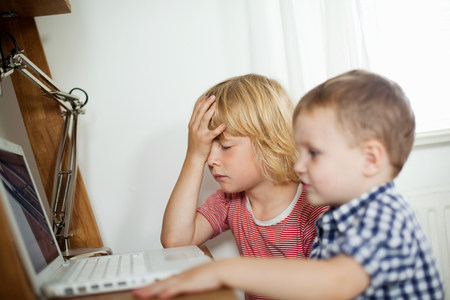 Young boys using laptop at desk