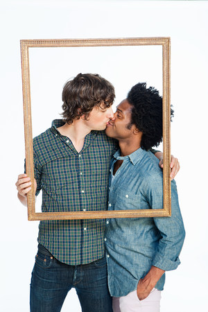 smooch: Gay couple kissing with picture frame against white background LANG_EVOIMAGES