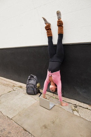 brown haired: Woman performing handstand and using laptop on pavement LANG_EVOIMAGES