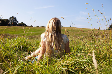Young woman sitting in a field with back to camera LANG_EVOIMAGES