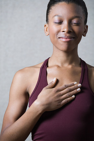 Women breathing deeply, touching chest LANG_EVOIMAGES