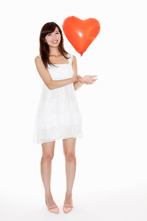 sultry: Woman holding red heart shaped balloon, studio shot