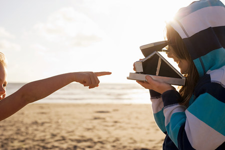 top 7: Girl pointing at friend with instant camera at beach