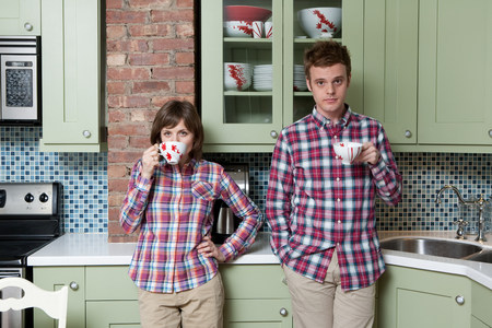 matching: Young couple holding teacups in kitchen