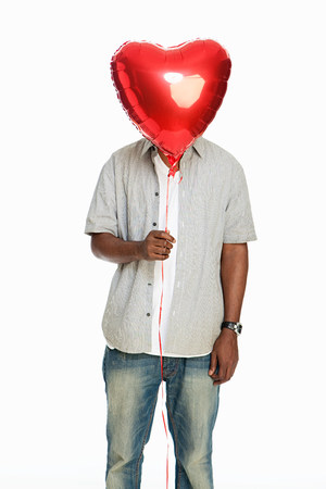 bashful: Mid adult man holding red balloon against white background