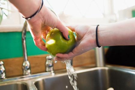 sinks: Teenage girl washing apple in kitchen sink