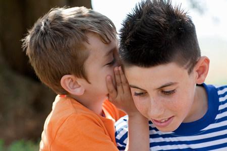 Boy whispering to firiend