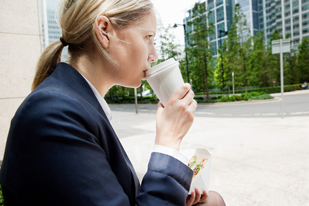 ponderous: Businesswoman with coffee and sandwiches LANG_EVOIMAGES