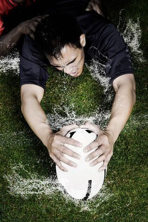 winning pitch: Rugby tackle on wet ground