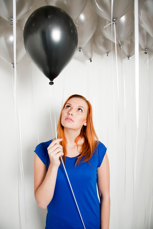 Young woman holding a black balloon LANG_EVOIMAGES