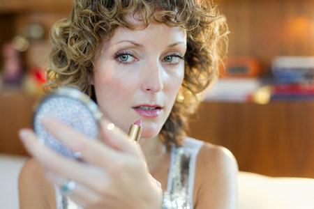 Mediados de mujer adulta aplicando lápiz labial