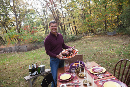 feast: Mature man with food for outdoor dinner