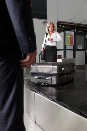 exasperation: Mid adult businesswoman waiting for luggage in airport baggage re-claim