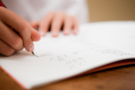 Close up of the hands of a young boy writing in a textbook