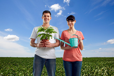 Couple in field with watering can and plant LANG_EVOIMAGES