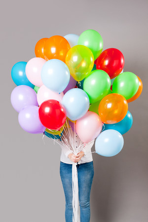 concealing: Woman holding large amount of balloons