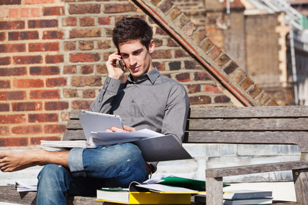 personal digital assistant: Young man sitting on a bench with a digital tablet and mobile phone