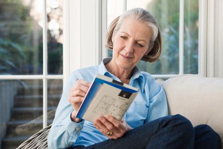 60 64 years: Senior woman doing sudoku puzzles