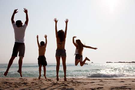getting out: Family jumping up in the air on a beach