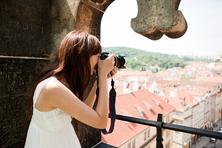 Woman photographing old town, Prague, Czech Republic