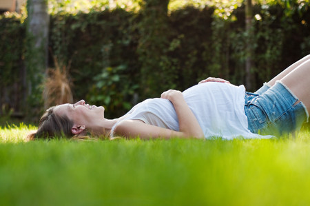 only 1 woman: Young pregnant woman lying on grass