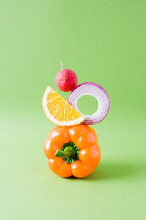 Arrangement of pepper, onion, orange and radish against green background
