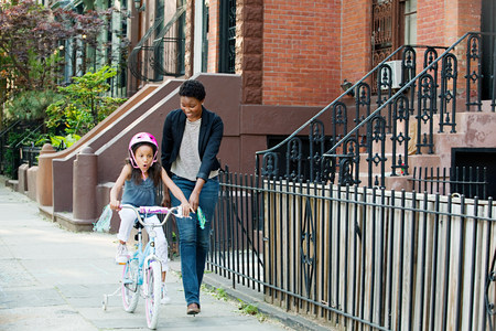 Daughter learning to ride bicycle along sidewalk with mother LANG_EVOIMAGES