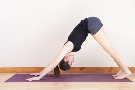 Woman in downward facing dog position during yoga LANG_EVOIMAGES