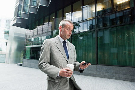 45 50 years: Businessman walking with smartphone and coffee