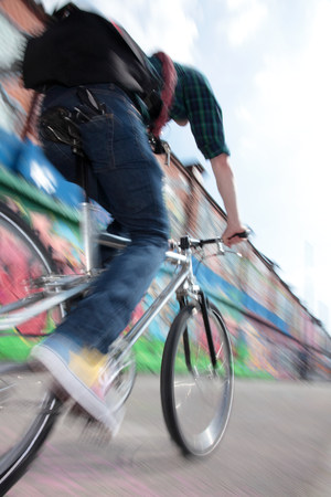 physically fit: Mid adult cyclist riding bike across bridge