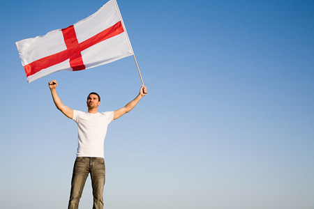Man holding St Georges Cross flag in the air LANG_EVOIMAGES