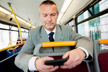 sayings: Businessman using smartphone on bus