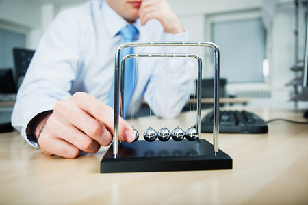 fedup: Office worker playing with newtons cradle