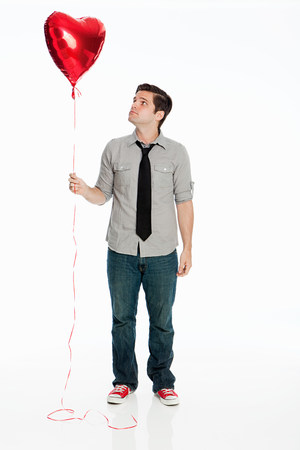 Young man holding balloon against white background LANG_EVOIMAGES