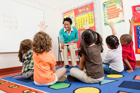 Teacher and children sitting on floors with hands raised