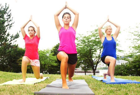 16 to 17 year olds: Three women practising yoga outdoors