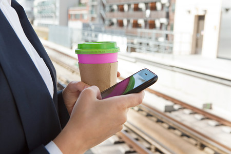 Close up of woman with coffee and smart phone in train station