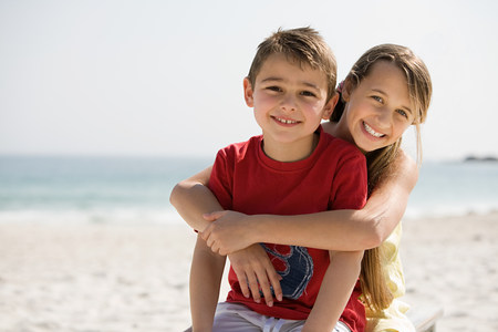 Brother and sister embracing on a beach LANG_EVOIMAGES