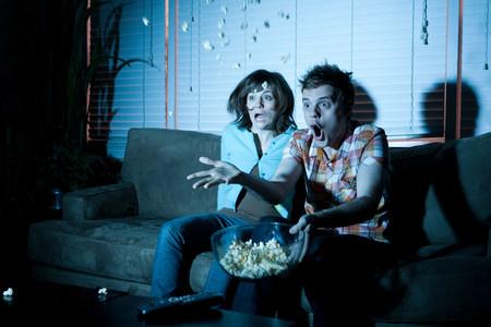 housing lot: Young couple watching tv, man throwing popcorn LANG_EVOIMAGES