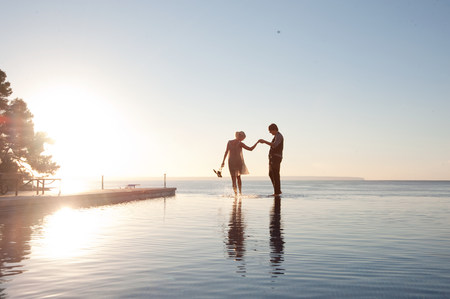 mirroring: Couple in the ocean at sunset