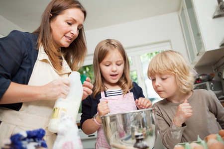 Mid adult woman baking with son and daughter in kitchen