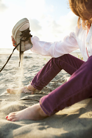 exasperation: Girl emptying shoe at beach