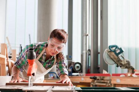 engrossed: Carpenter using saw in workshop LANG_EVOIMAGES