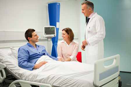 Wife visiting husband in hospital, talking to doctor