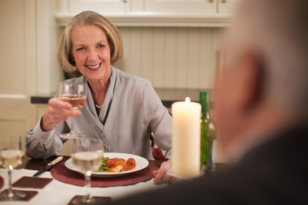 60 64 years: Senior woman with wine at dinner
